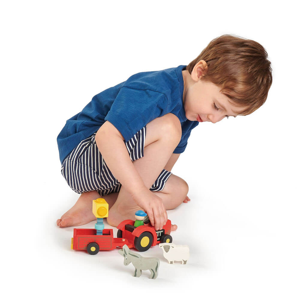 Boy playing with the Tender Leaf Toys Tractor & Trailer