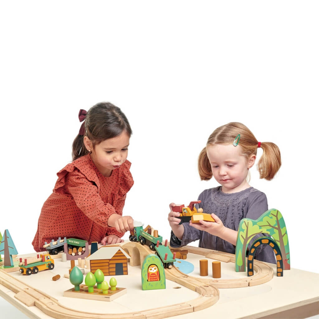 Two girls playing with the Tender Leaf Toys Wild Pines Train Set