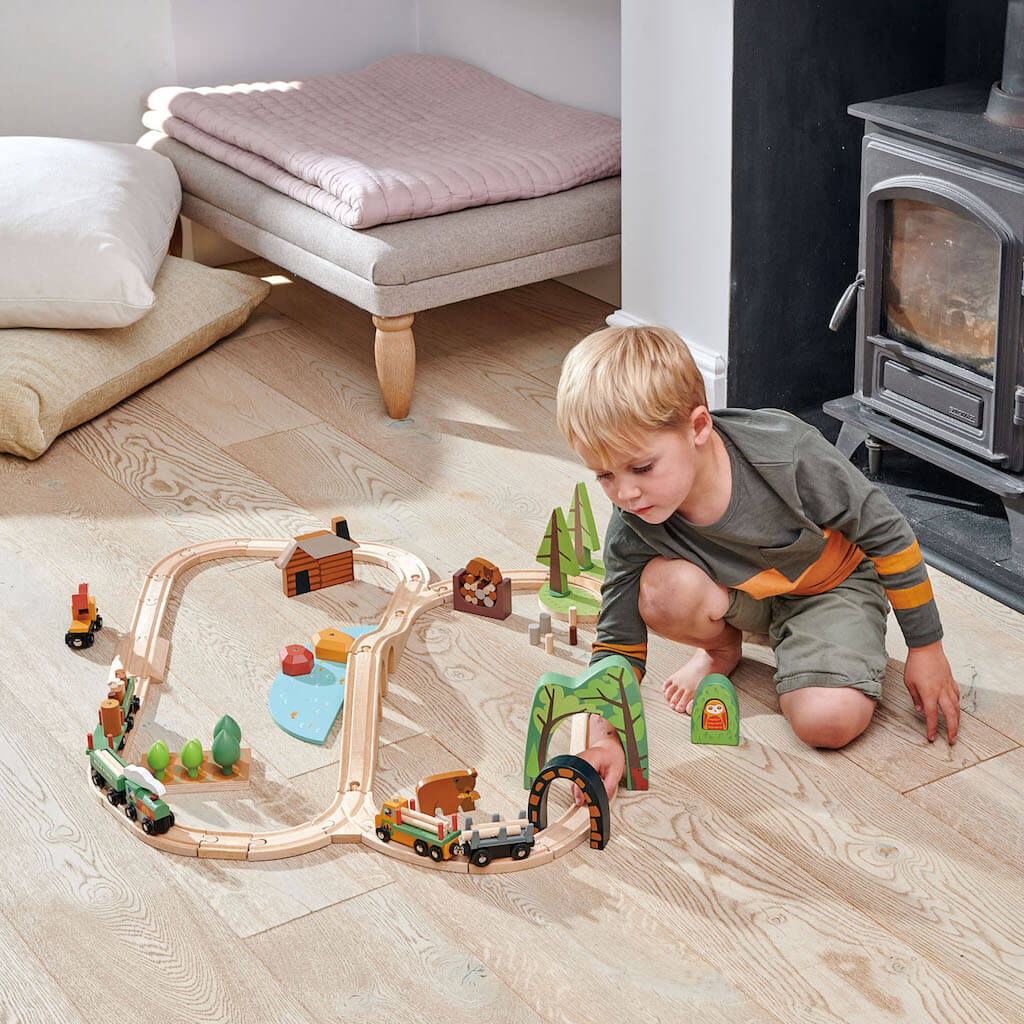 Boy playing with the Tender Leaf Toys Wild Pines Train Set