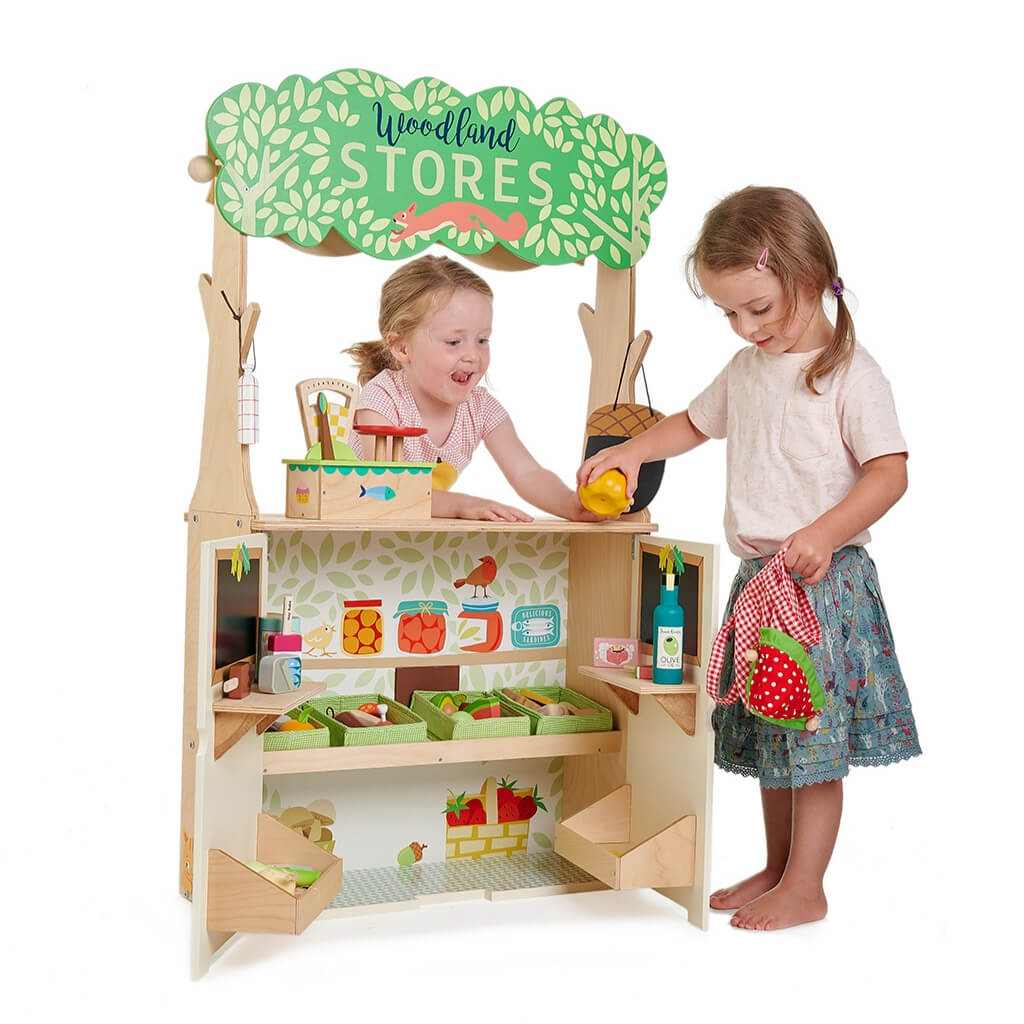 Two girls playing with the Tender Leaf Toys Woodland Stores and Theatre