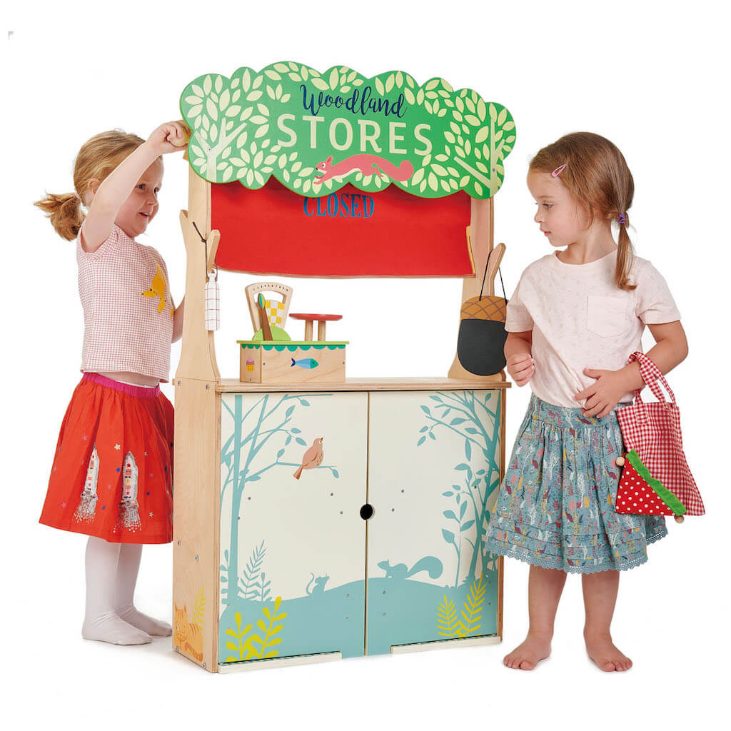 Two girls closing the Tender Leaf Toys Woodland Stores and Theatre