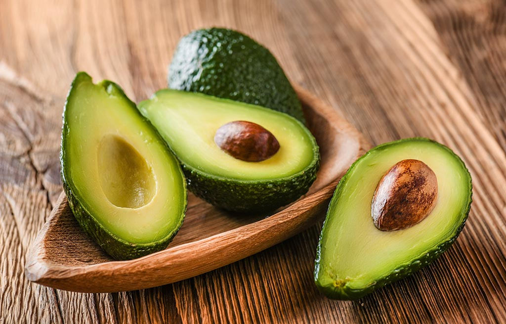 Avocado Split in half and kept in a bowl on a wooden table