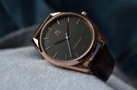 Close up of a rose gold watch with a charcoal coloured face and brown leather strap