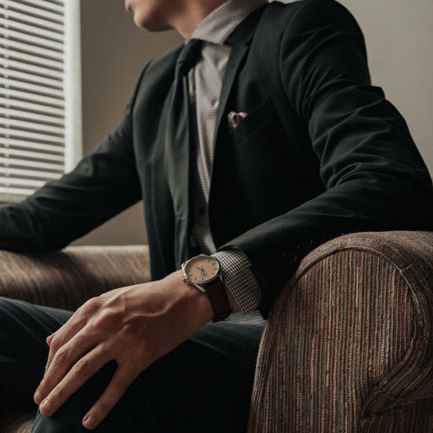 Man wearing a dark coloured suit and tie wearing an Archer Benson watch on his left wrist