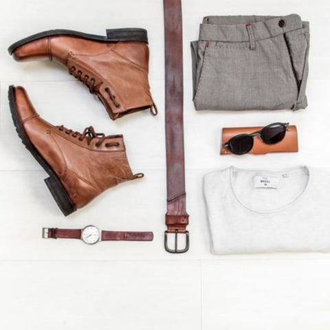 A pair of brown work boots, a brown belt, folded pants and white shirt, and a watch arranged neatly on a white surface.