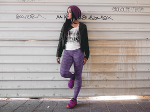 Hip young woman standing beside a grungy wall wearing leggings for women, Vintage Trailers, two-tone purple