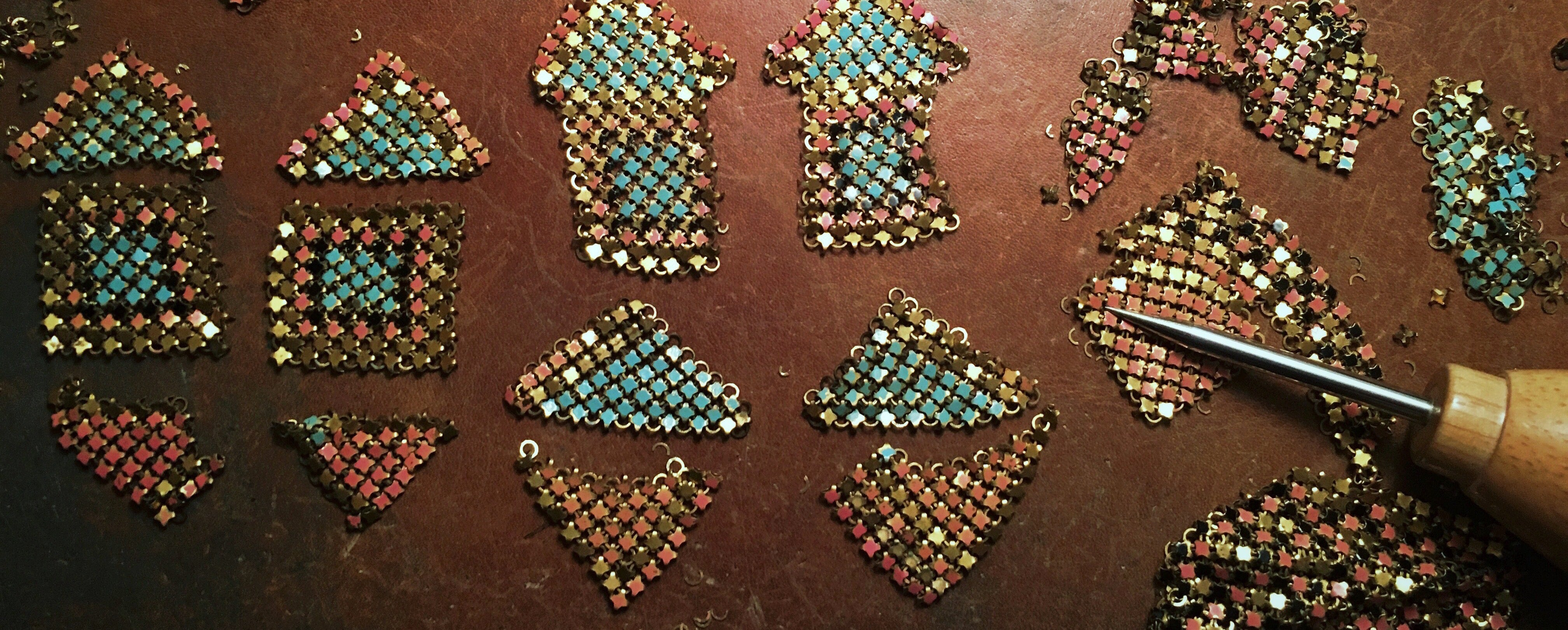 Process shot of antique metal mesh being pieced into earring forms.