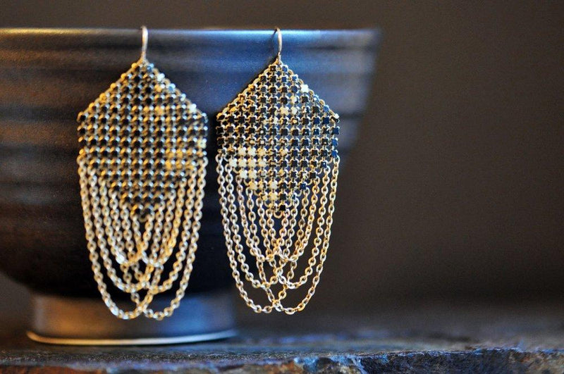 Lifestyle view of Swagged Lantern Mesh Earrings in Faded Black, handmade by Maral Rapp with enamel metal mesh recycled from an antique mesh purse.