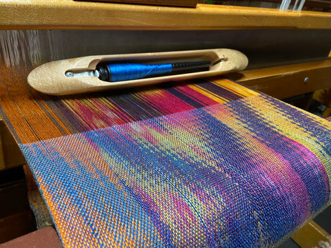 Brightly colored weaving in yelllow, navy, neon orange and blue.