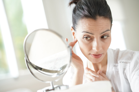 Woman inspecting Face Wrinkles in bathroom mirror