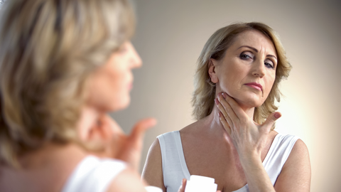 Mature women applies skincare product to neck. Anti aging treatment