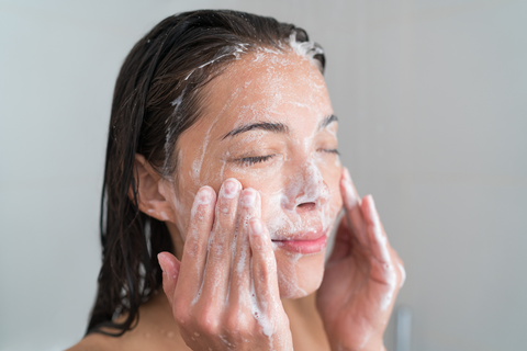 Woman deep cleansing and exfoliating skin to prevent adult acne
