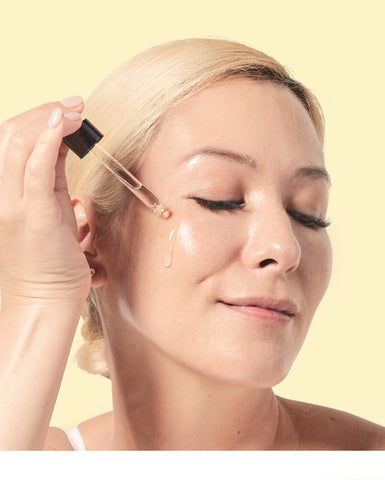 Woman applying Oia Vitamin C serum
