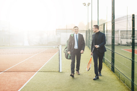 Two people with tennis racquet bags on a tennis court