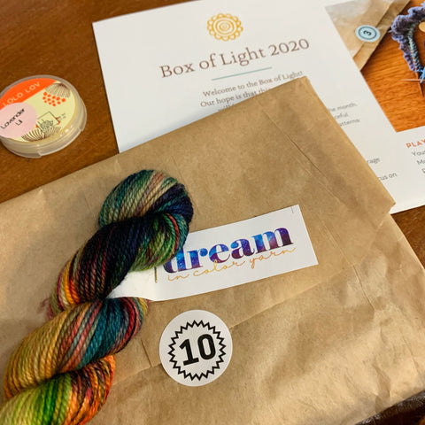 an open envelope with a number 10 sticker, a mini skein from Dream in Color, a Lolo Bar sample and a portion of the Box of Light pattern from 2020 all out on a table waiting to be worked on