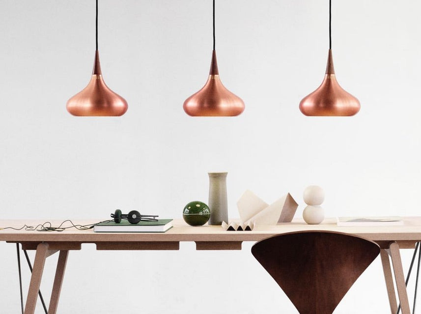 3 Fritz Hansen Orient Copper Lights hanging over dining table
