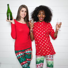 Two ladies in christmas leggings with a bottle of champagne and 2 glasses raised.