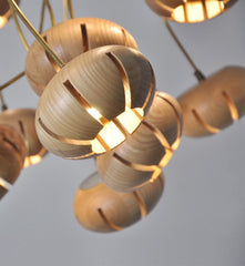 Wooden flower petal strip on copper wire pendant light close up light wood