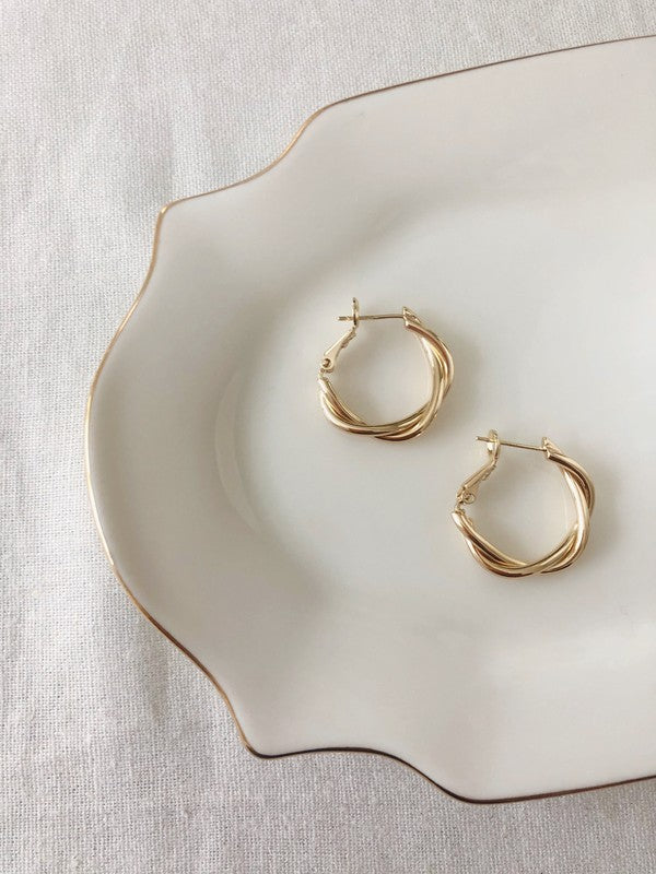 Elegant Classic Timeless Chic 14K Twisted Gold Hoop Earrings on a porcelain dish
