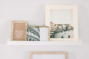 Three framed art pieces of varying sizes on a ledge