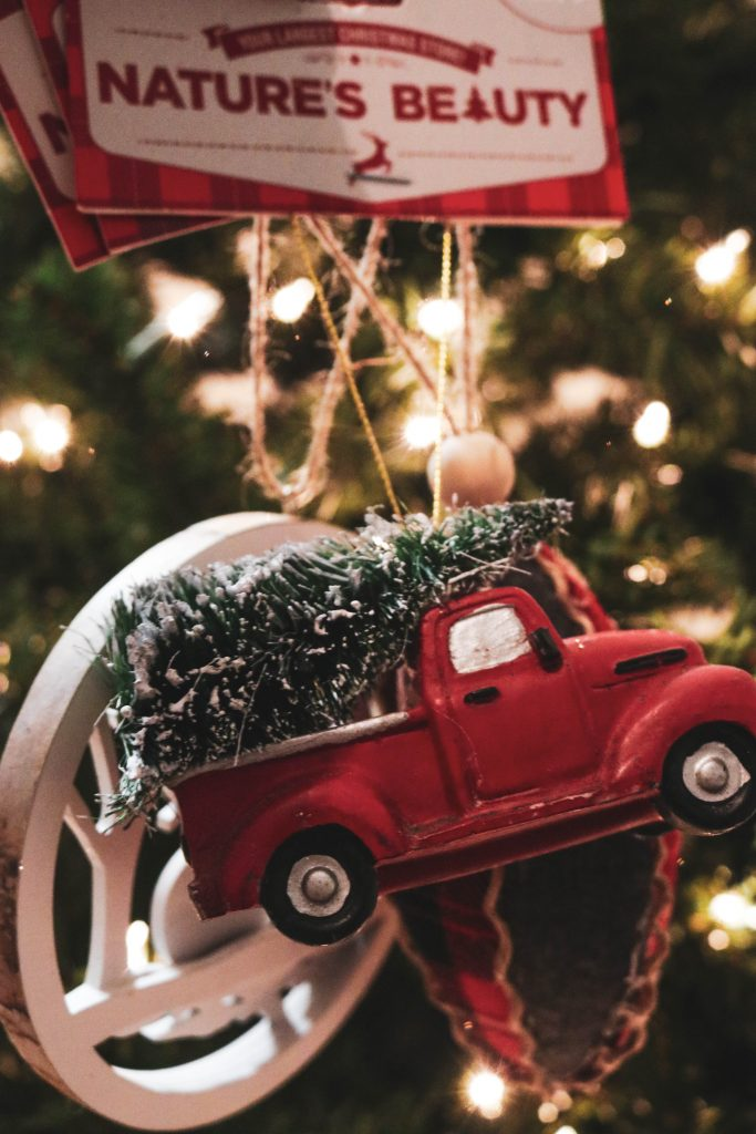 A handmade ornament depicting a truck carrying a Christmas tree