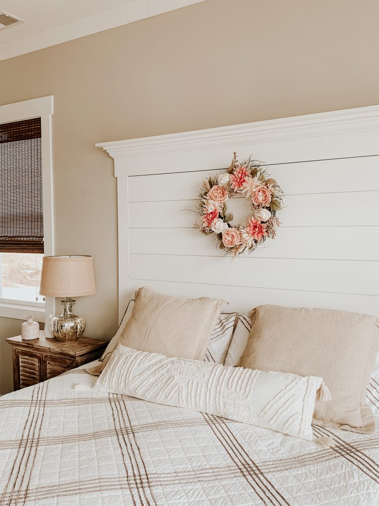 A blush and cream wreath hanging on the bed's headboard