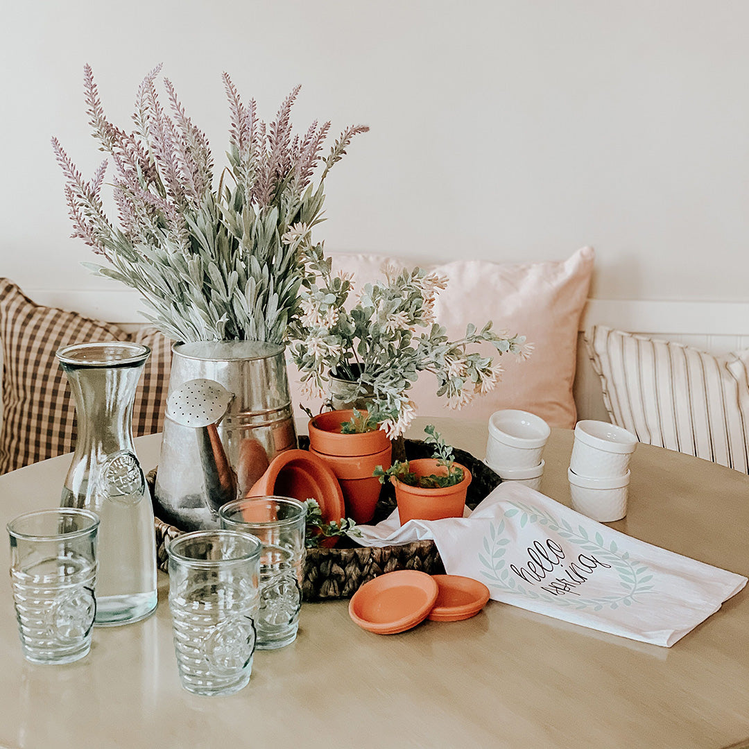 Breakfast nook topped with rustic decor including drinking glasses, a pitcher, terracotta planters, and a kitchen towel.