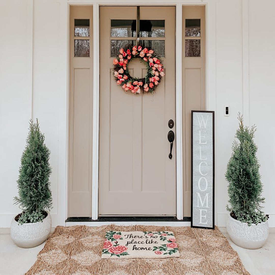 Spring front porch decor with a door mat, stand up welcome sign, a pine tree in ceramic planters on each side of the door and a pink rose wreath on the door.