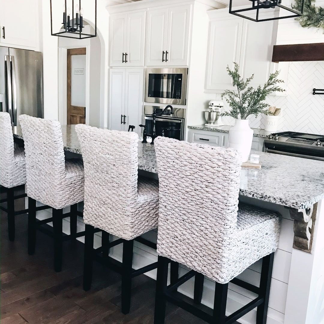 Wicker barstools pulled up to a farmhouse style marble bar.