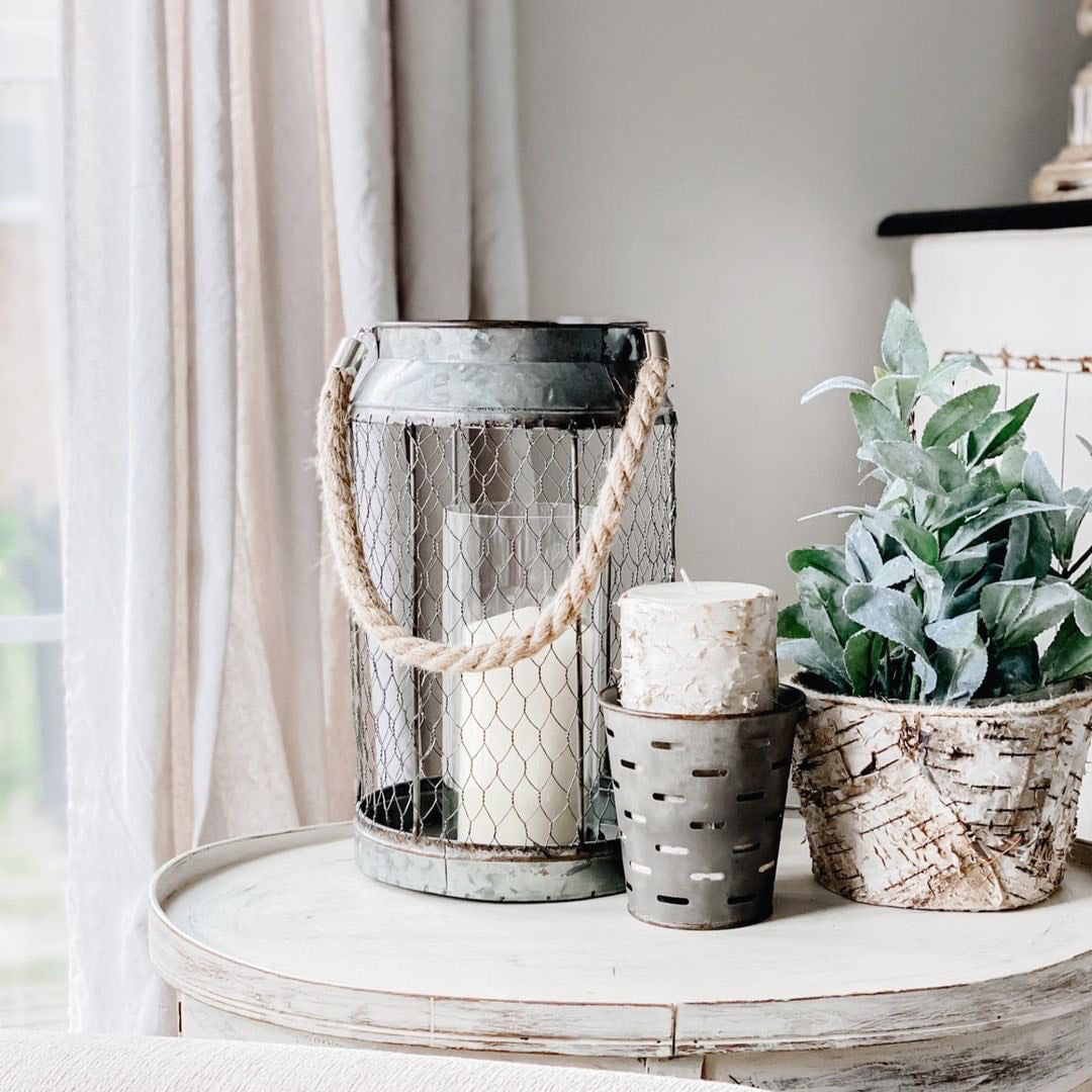 On a side table there is a rustic lantern, candle, planter, and faux greenery.