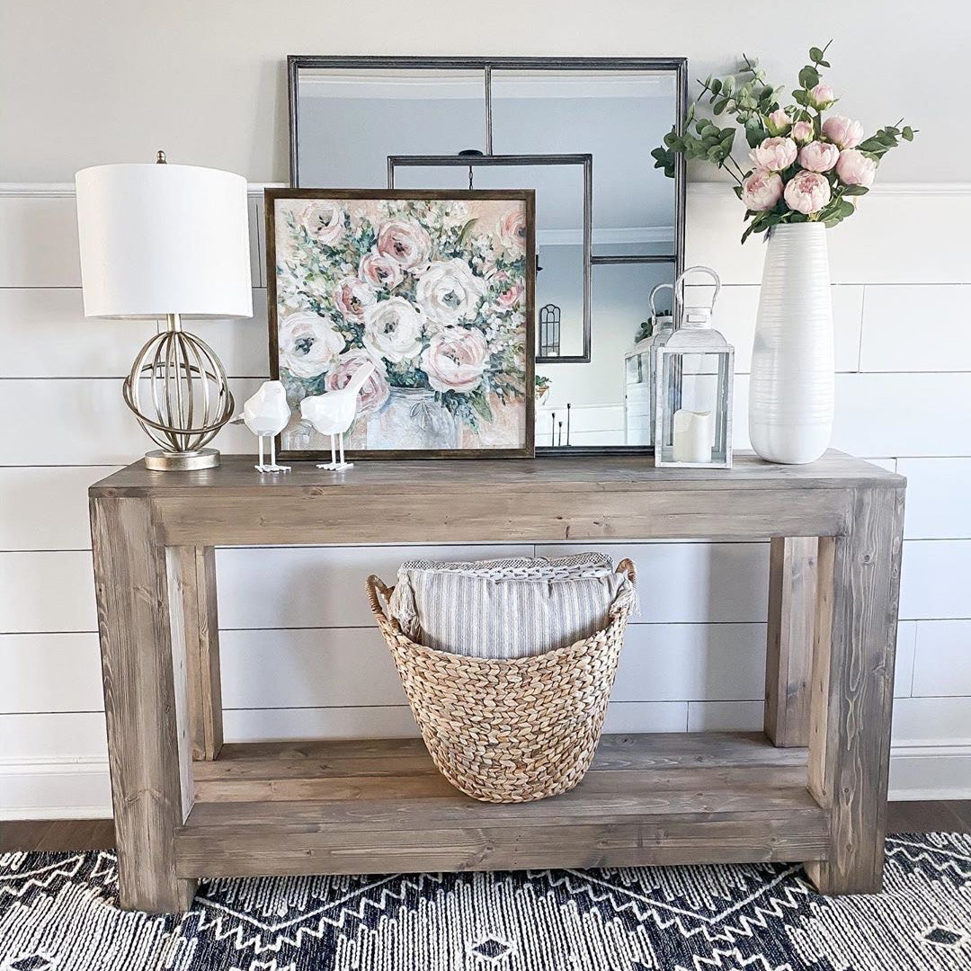Entryway table with a lamp, wall decor, a vase, pink floral, and a wicker basket.