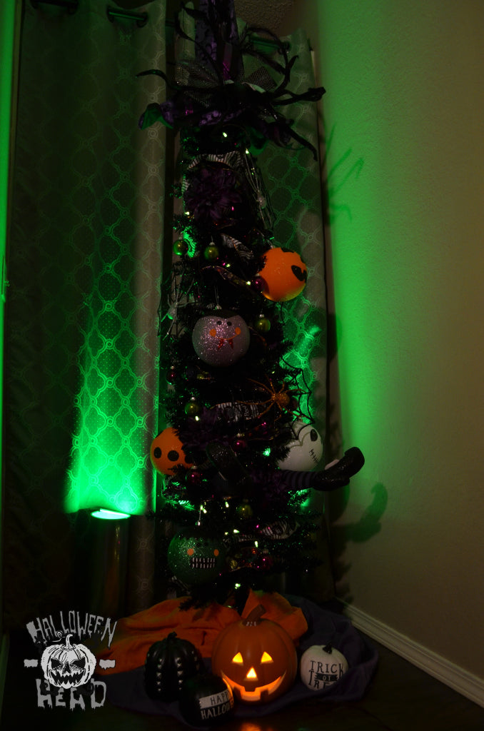 Green light bathes the spooky Halloween tree
