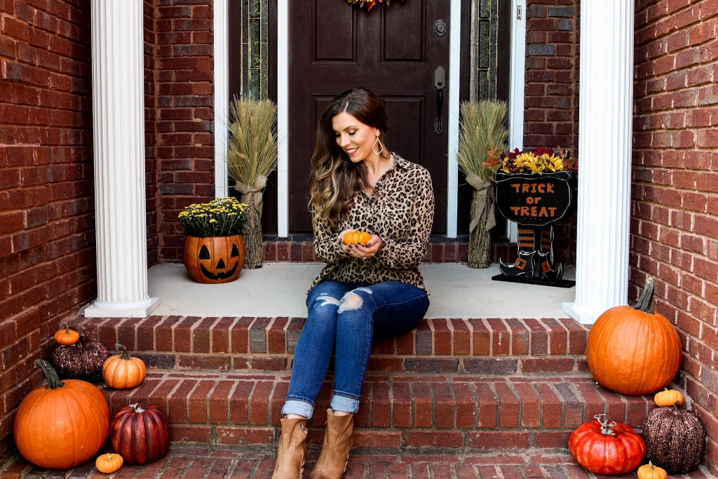 Savilla Mountain sitting on her porch with fall décor