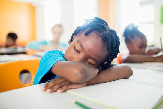 African american child in a classroom asleep