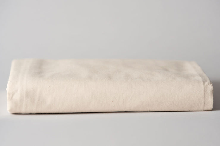 Organic cotton crib sheets in natural color folded.