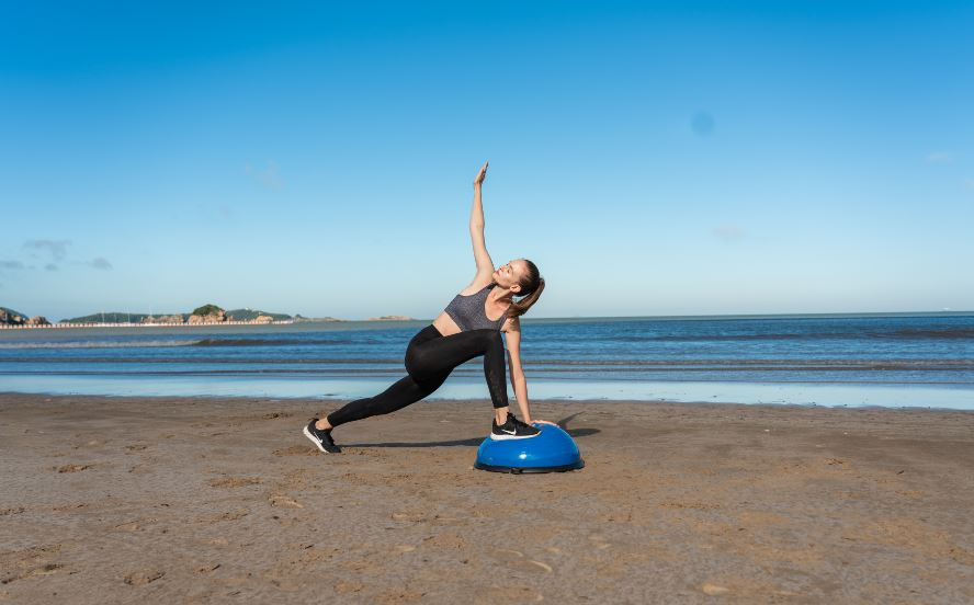 woman doing a yoga pose on a half balance ball
