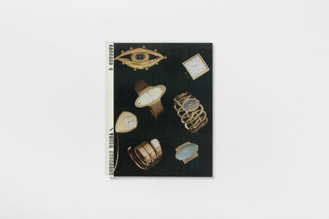 A book with a white spine and photographs of watches on a black background on the cover