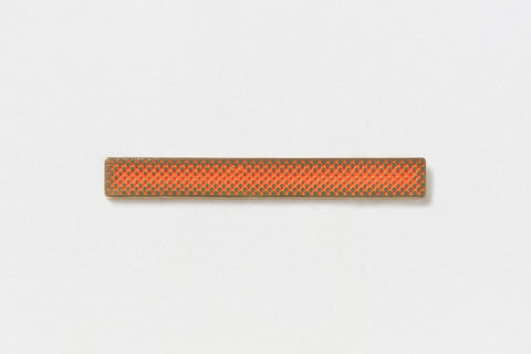A long rectangular gold pin with a central orange gradient