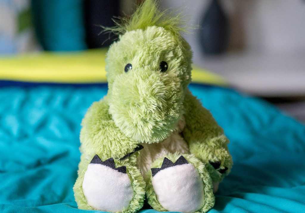 "Warmies® 13"" Dinosaur Stuffed Animal sitting on a bed"