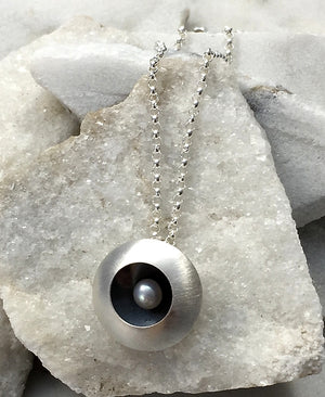 EMMA TALLACK JEWELRY —  Handcrafted Double-Domed, Brushed Sterling Silver and White Button Pearl Pendant / Necklace with Oxidized Center — 1.5 centimeters