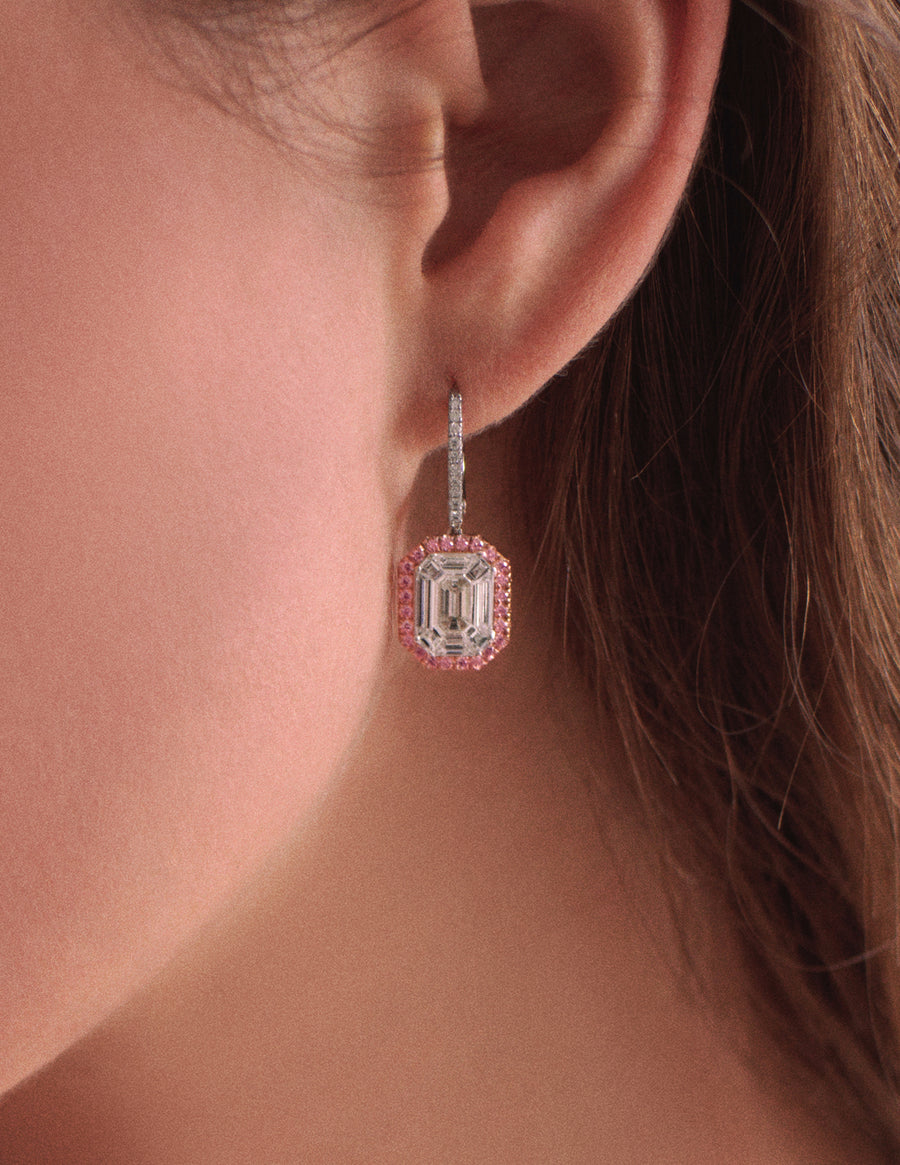 Fashion model wearing invisibly set emerald cut diamond halo earrings with pink diamonds from JFINE.