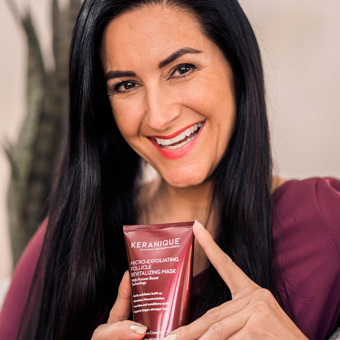 Smiling woman holding a bottle of Keranique Micro-Exfoliating Follicle Revitalizing Mask