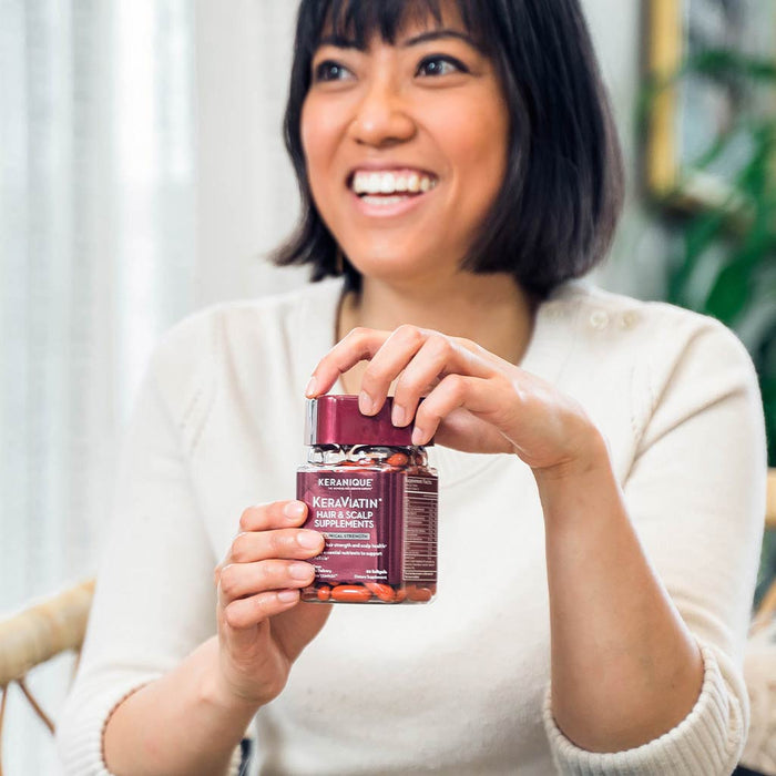 Photo of smiling woman holding a bottle of KeraViatin Hair and scalp supplements