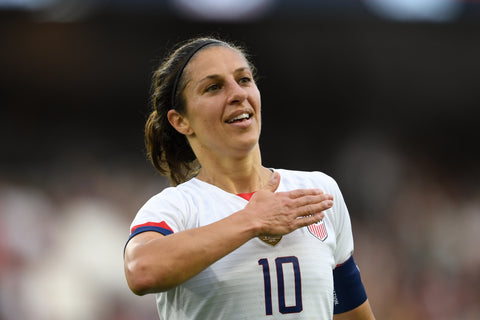 Carli Lloyd beating her chest with her hand to thank the public