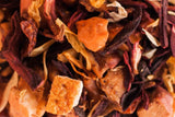 Loose leaf tea with red, orange and yellow leaves and dried fruit.