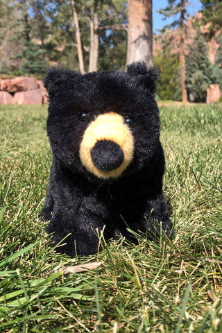 Front view of a black bear stuffed animal toy in the grass with rocks and trees in the background.