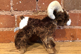 A stuffed bighorn sheep toy in front of bricks.