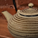 Close up of a cream colored tea pot with gold lines.
