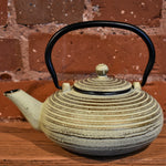 Cream colored cast iron tea pot with a lid and a black handle.