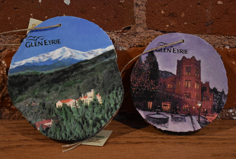 Two wooden ornaments featuring scenes of Glen Eyrie Castle.